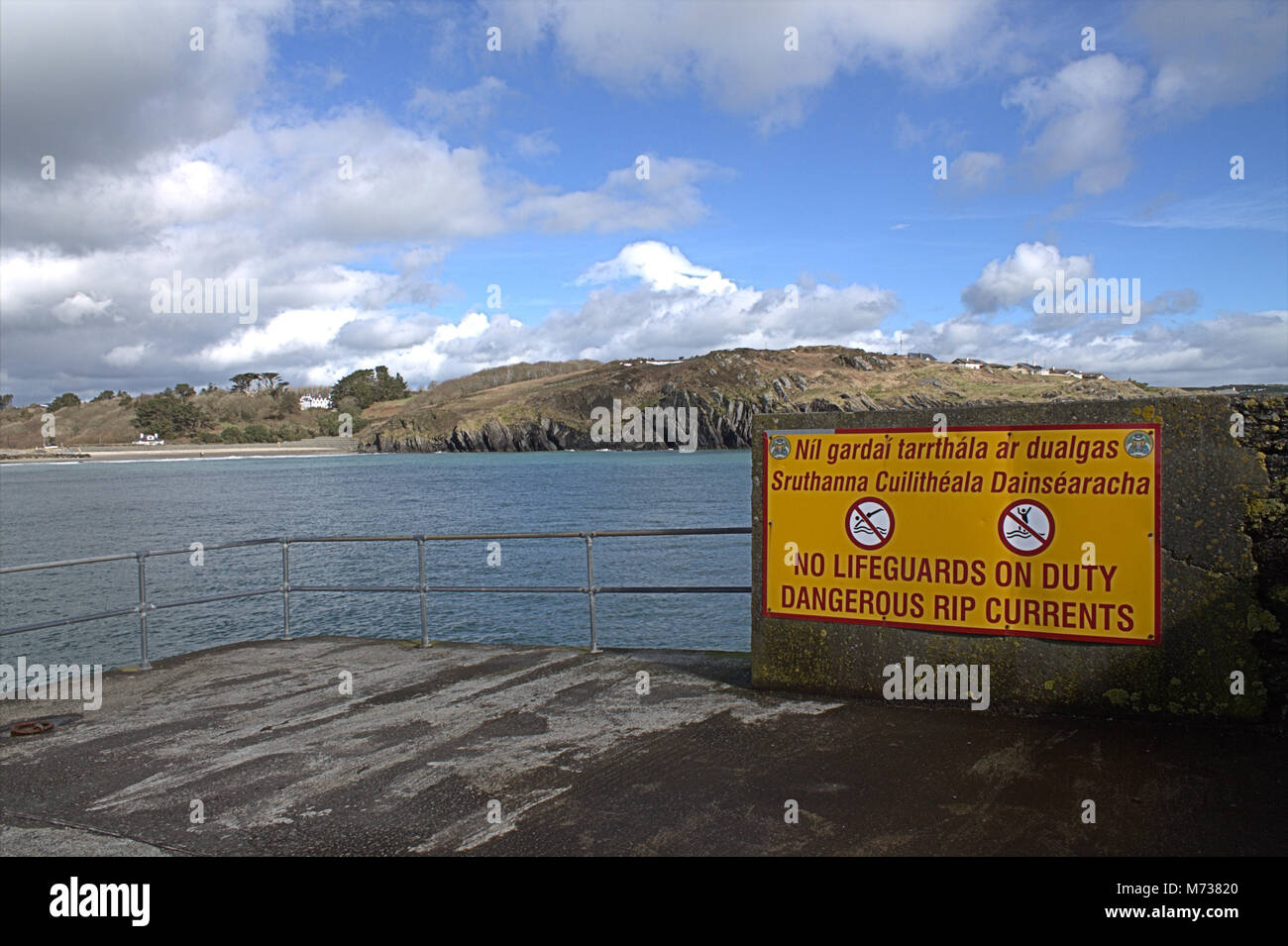 Danger Rip Tides sign in English and Gaelic. The sign is at the end of a jetty in Rossbarbery, Ireland, where the - Stock Image