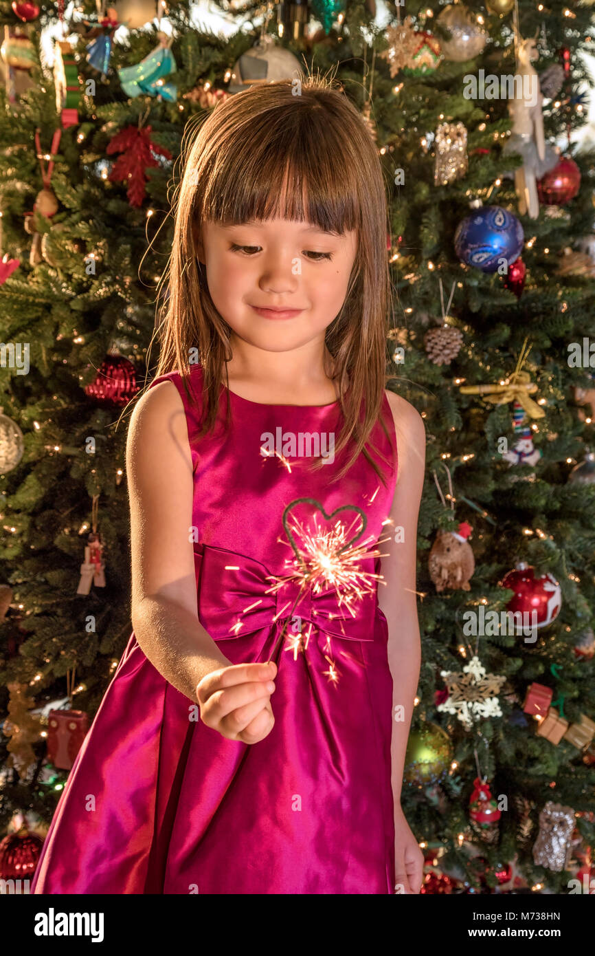 Five year old girl holding a heart shaped sparkler at Christmastime - Stock Image
