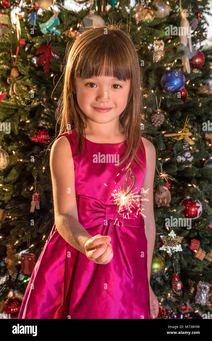 Five year old girl holding a heart shaped sparkler at Christmas Eve - Stock Image