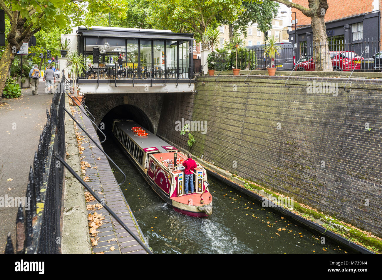 A canal narrowboat disappears into the Maida Hill Tunnel on the Regent's Canal, Maida Vale, London, UK.  The - Stock Image