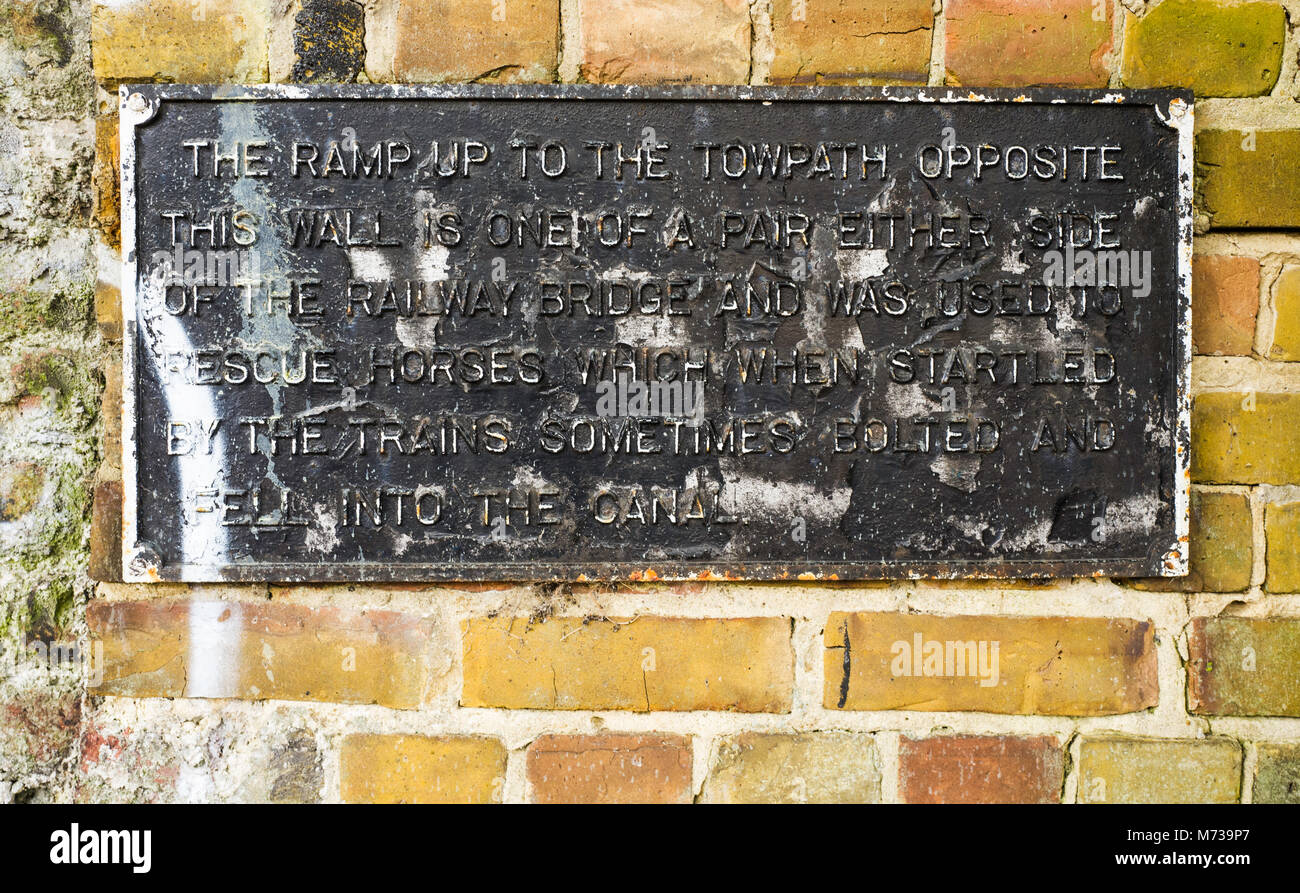 A plaque on the towpath of Regent's Canal describes a ramp up to the towpath which was used to rescue horses - Stock Image
