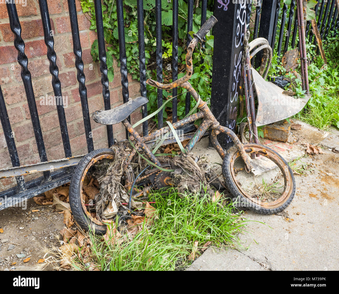 An abandoned children's bicycle at the side of the Regent's Canal towpath, Lyme Terrace, near Camden Town, - Stock Image