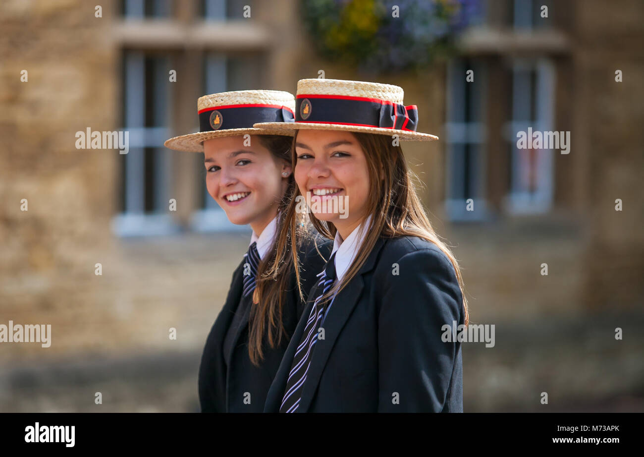 Two English Public Schoolgirls wearing boaters on a sunny day, with old stone buildings in the background - Stock Image