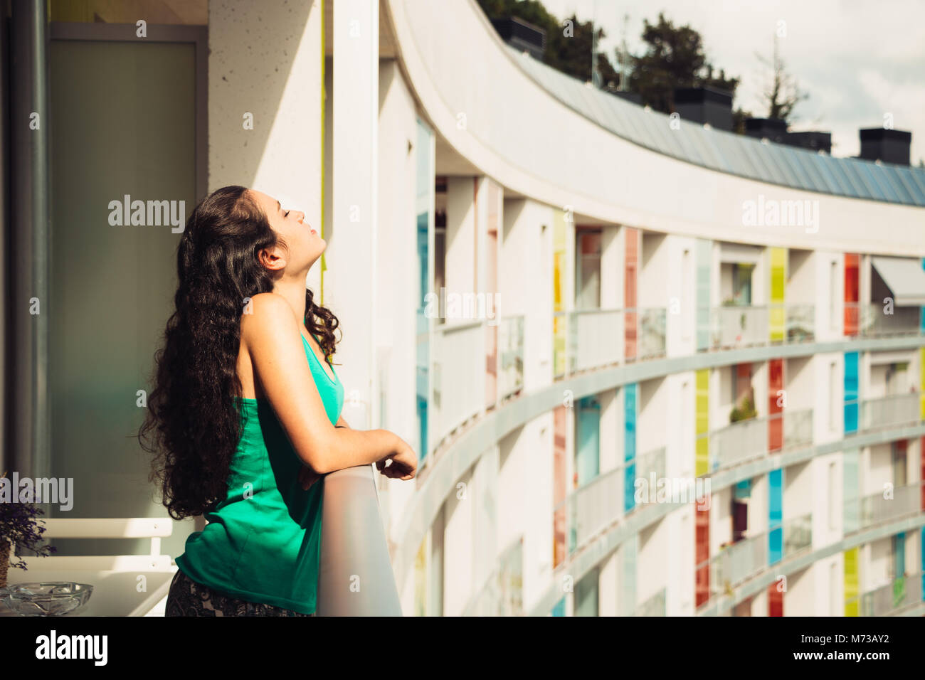 Young woman leaning on the balcony in her apartment to sunbathe - Stock Image