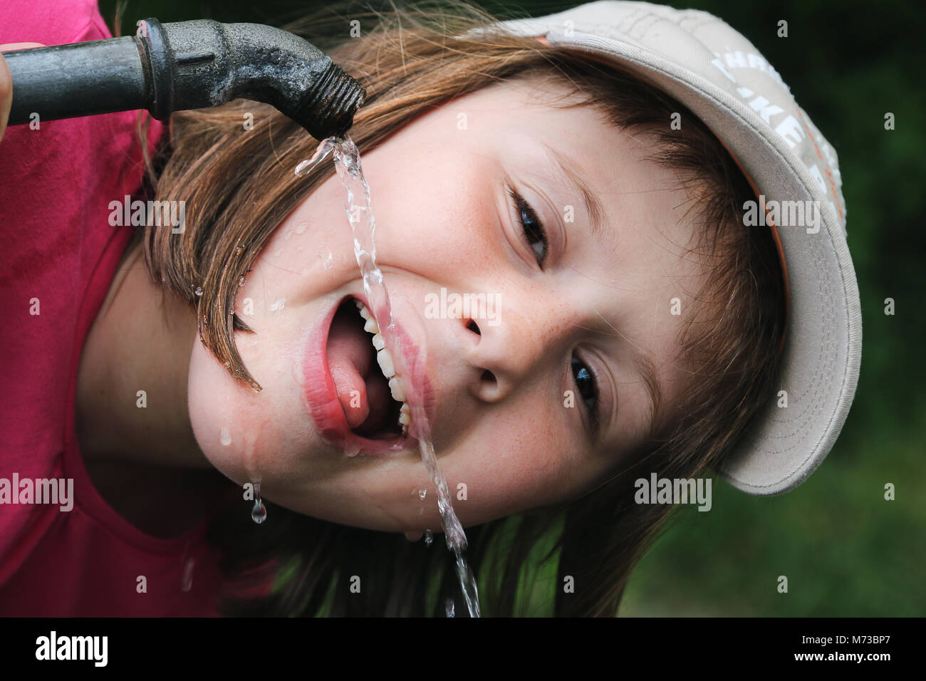 Young girl 8-10 years old drinking water out of the water pipe outside to refresh herself. Clean drinking water - Stock Image