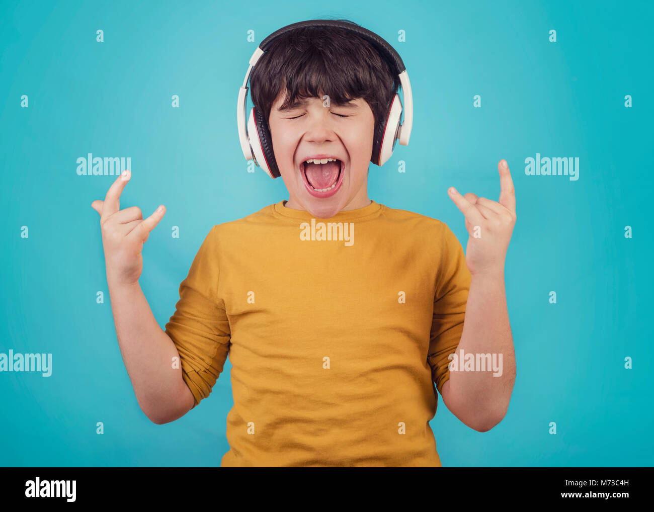Boy with headphones showing rock sigh - Stock Image