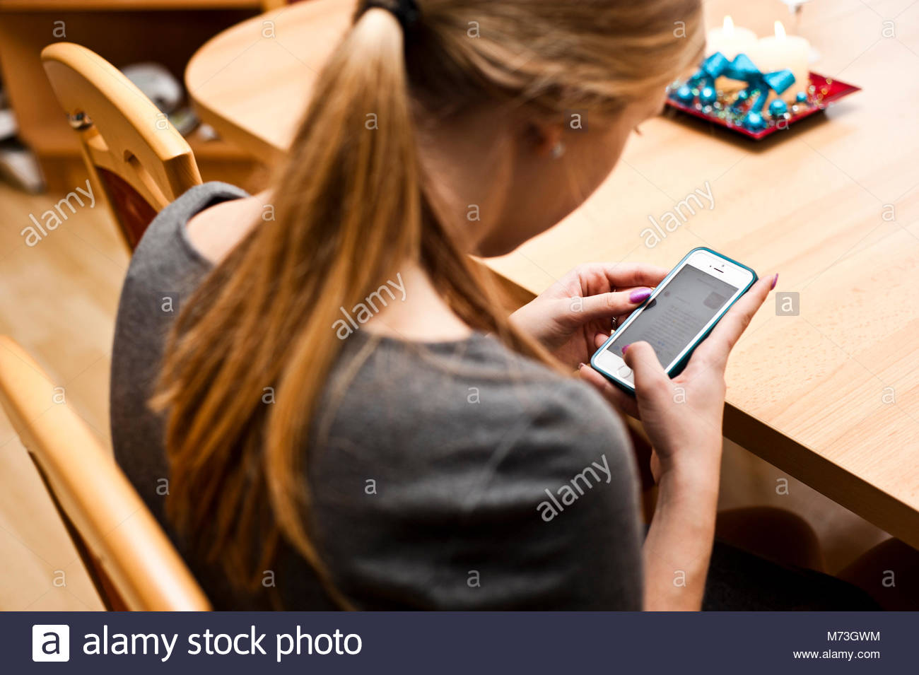 blond young woman messaging on her cellphone - Stock Image