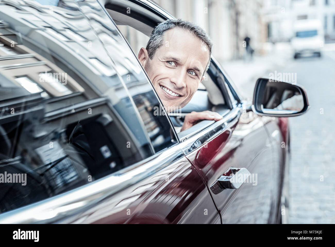 Positive cheerful man looking out from the car window - Stock Image
