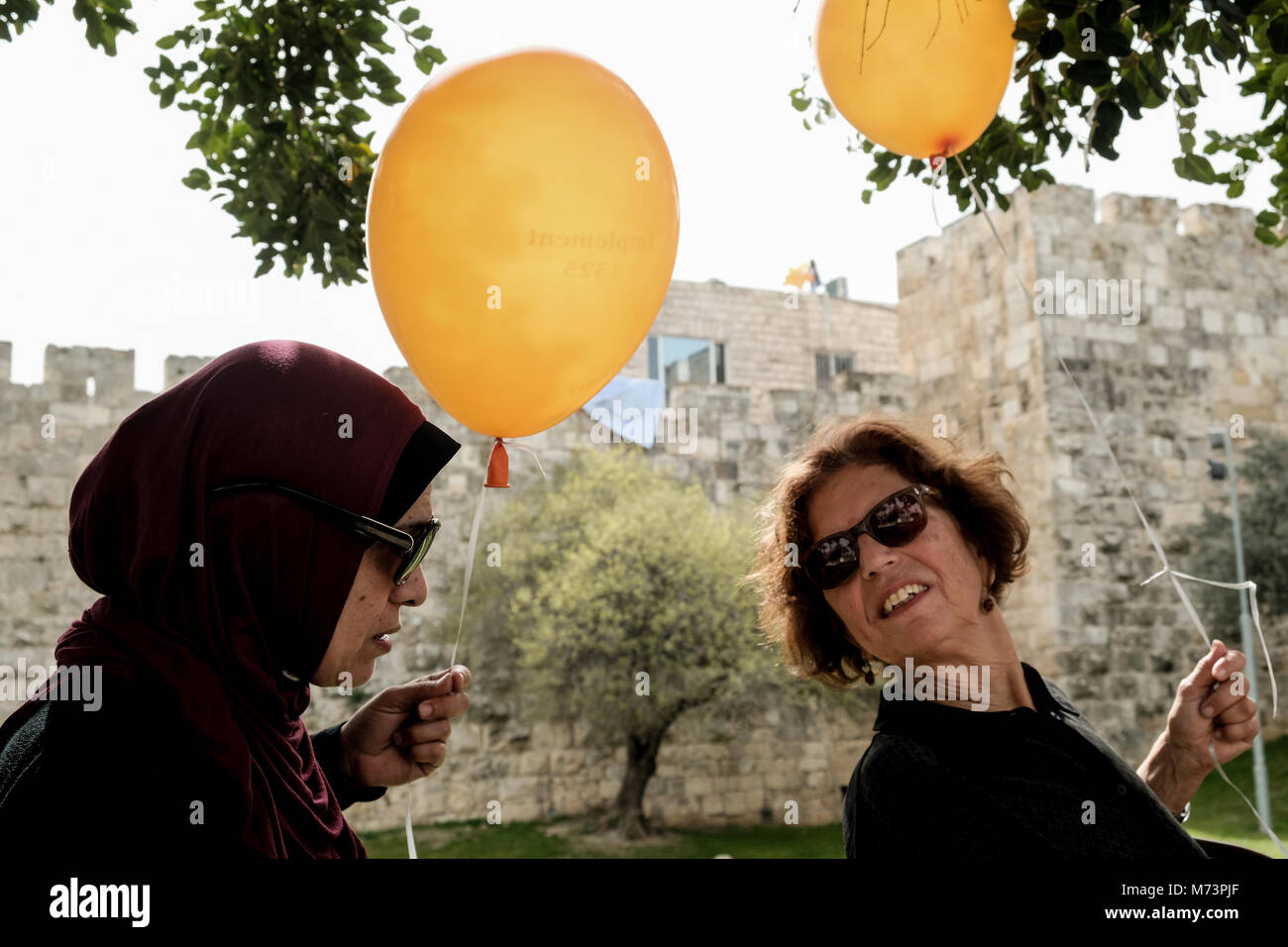 Jerusalem, Israel. 8th March, 2018. Palestinian and Israeli women stand together on International Women's Day - Stock Image