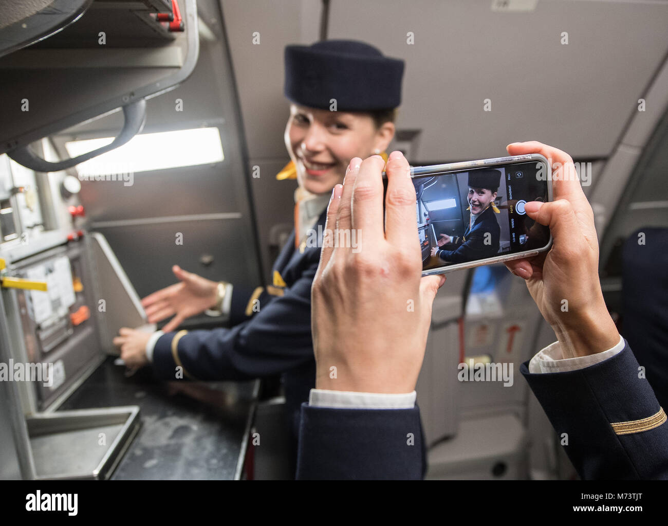 08 March 2018, Germany, Frankfurt: A stewardess takes a photo of her colleague in the Airbus A 321 flight to Berlin. - Stock Image
