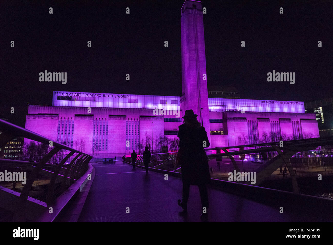 London, UK.  8 March 2018.  Tate Modern (pictured) and Tate Britain are lit up in a magenta colour to mark International - Stock Image