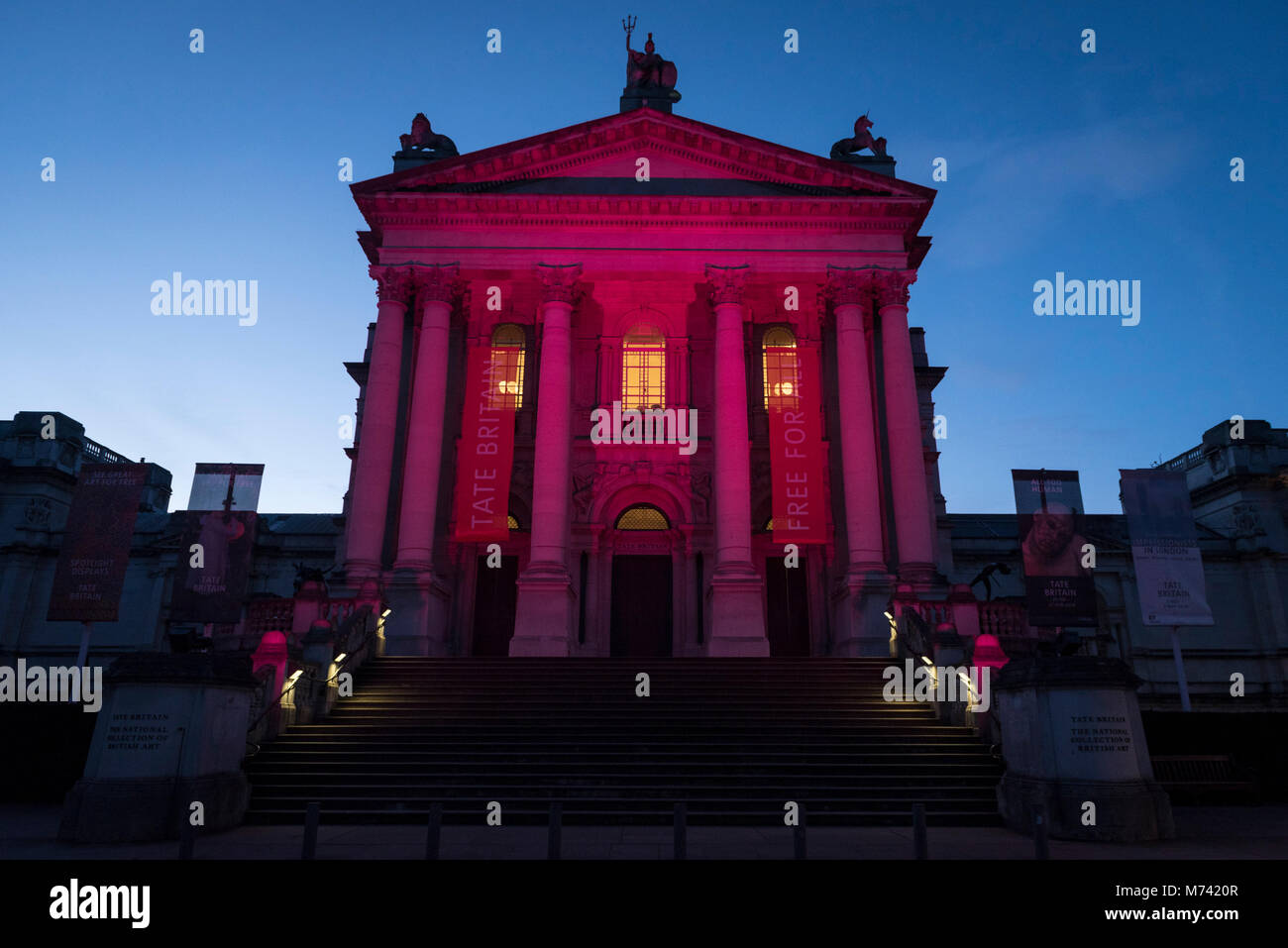 London, UK.  8 March 2018.  Tate Modern and Tate Britain (pictured) are lit up in a magenta colour to mark International - Stock Image
