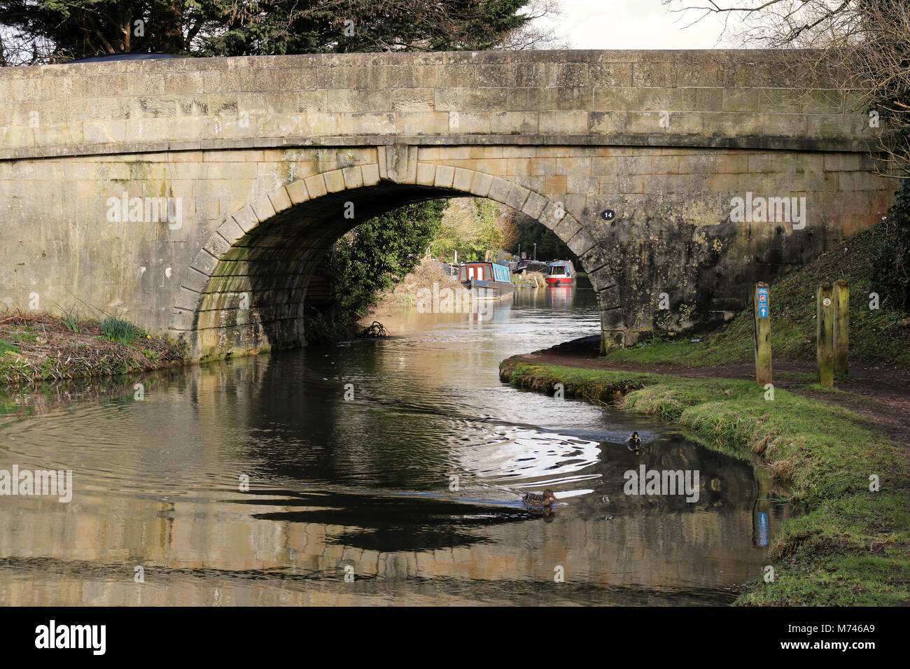 Kennet & Avon Canal in west Berkshire with quaint stone road bridge crossing the canal - Stock Image