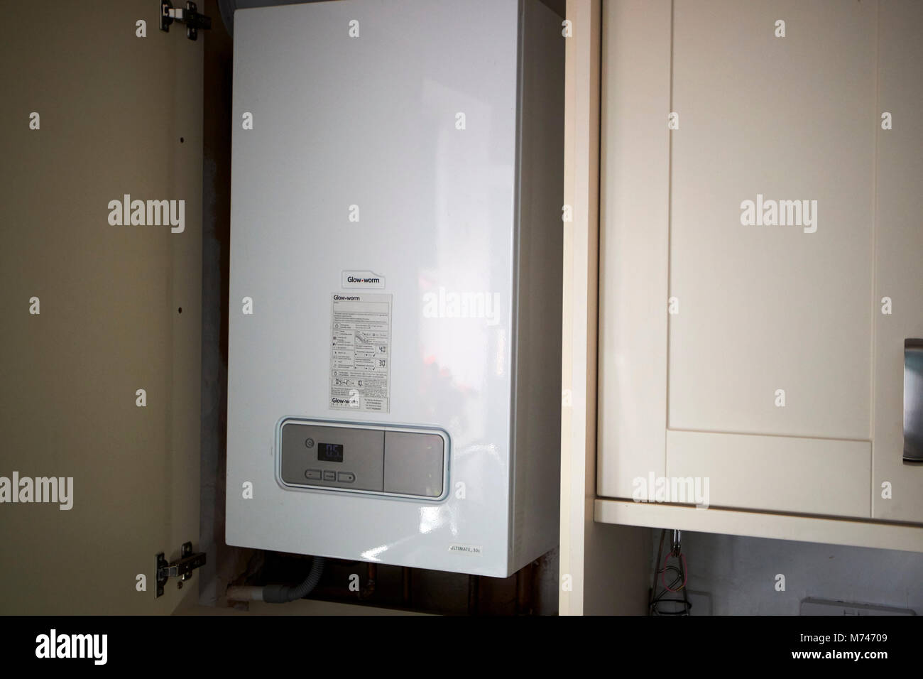 household combi gas heating and hot water supply boiler housed in a kitchen cabinet in a new kitchen newbuild in - Stock Image