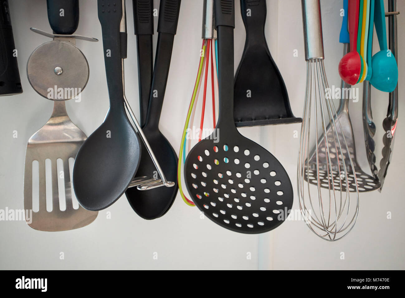 variety of kitchen utensils hanging on a rack in a kitchen in the uk - Stock Image
