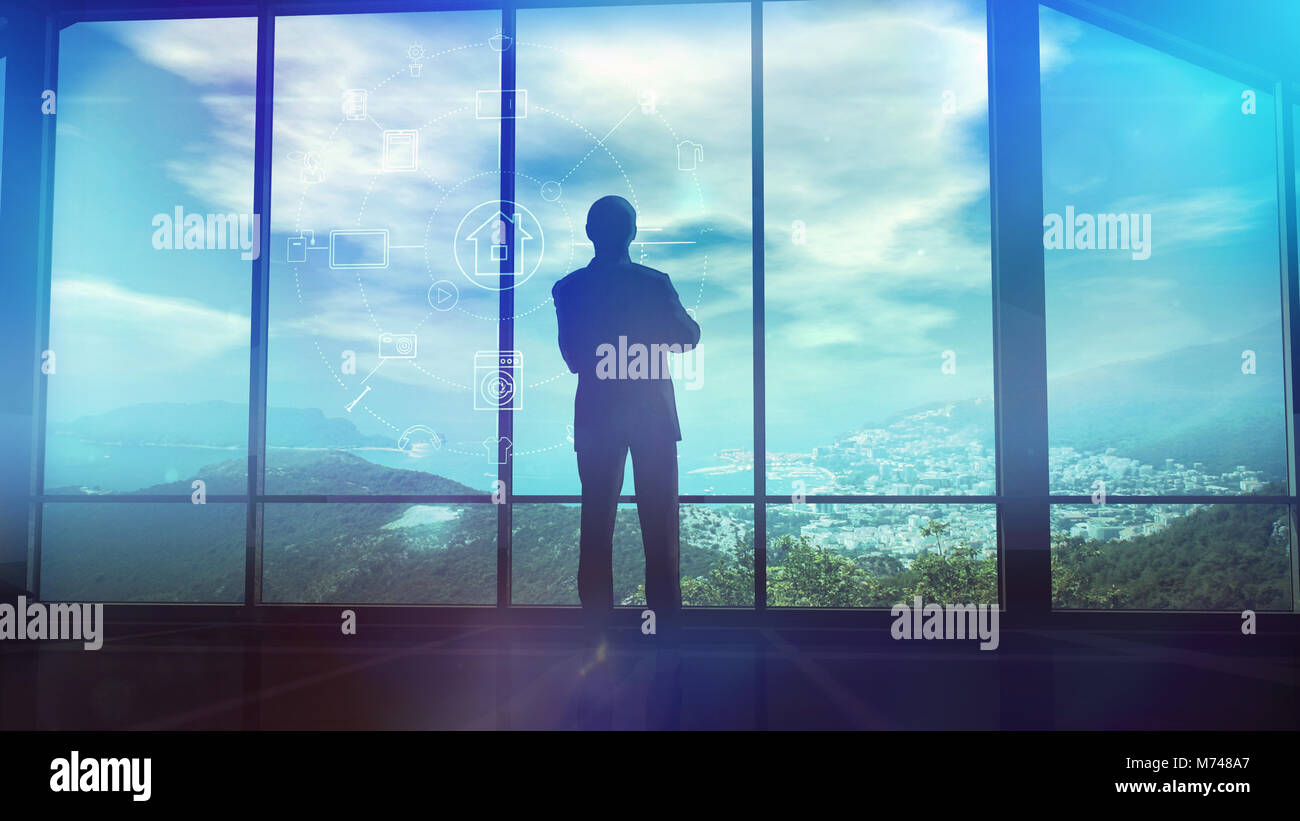 A man is standing by the window viewing IOT infographics elements - Stock Image
