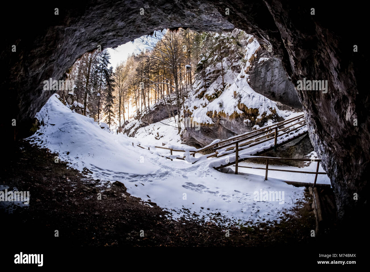 View from dark cave to snow covered gorge Baerenschuetzklamm with forest and wooden bridge in winter - Stock Image
