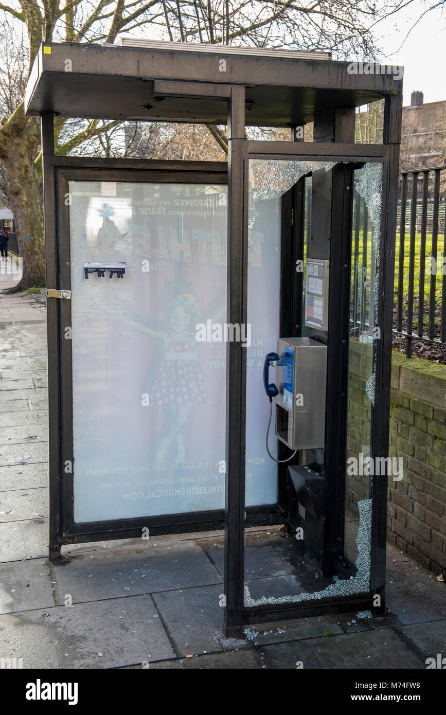 A broken or vandalised telephone kiosk or booth call box with broken g;lass and smashed doors and windows. Vandals - Stock Image