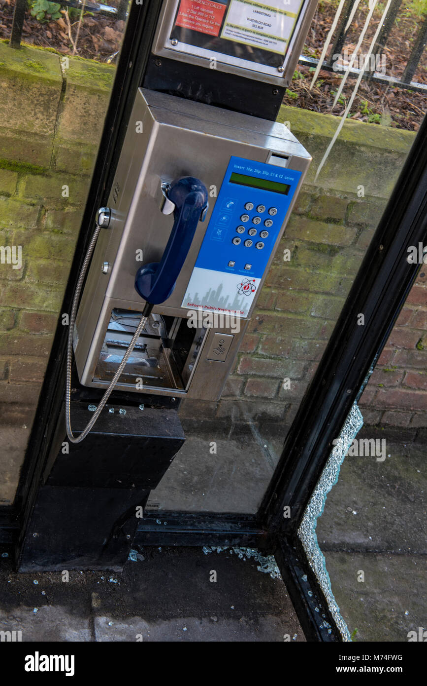 a vandalised phone or call box with broken glass and smashed window. Public call box telephone kiosk with broken - Stock Image