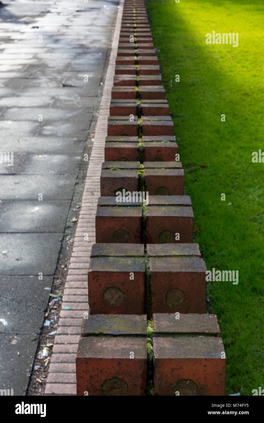 the top of a brick wall made from red bricks and gradually tapering away into the distance with grass on one side - Stock Image