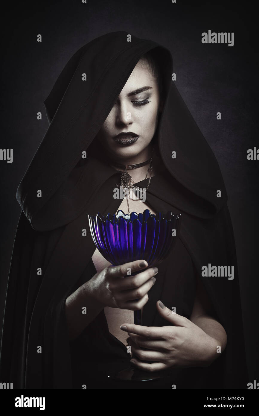 Beautiful vampire with a ritual cup. Hooded figure - Stock Image