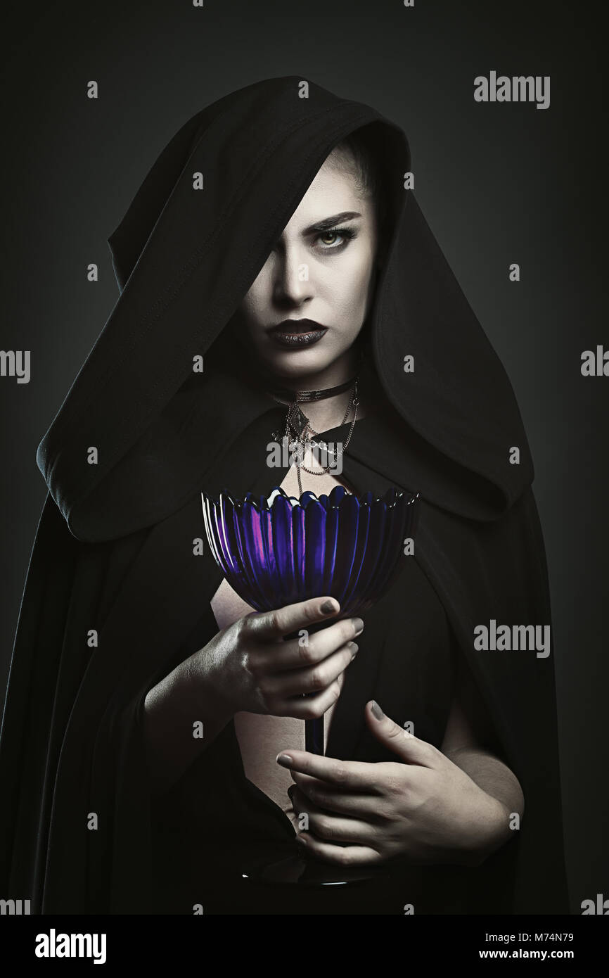 Beautiful vampire holding a cup. Blood ritual - Stock Image
