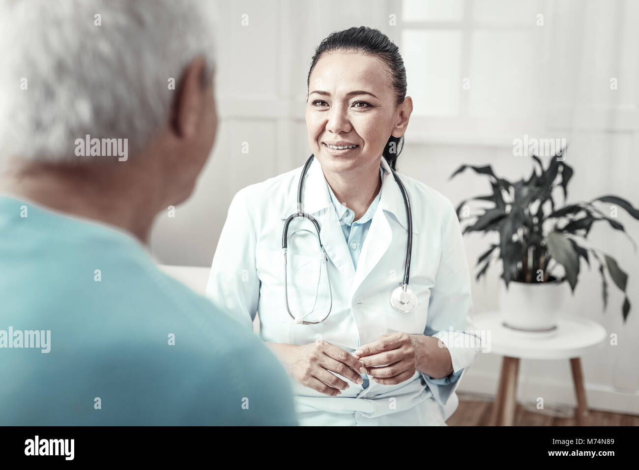 Skilled cute nurse smiling and having consultation. - Stock Image