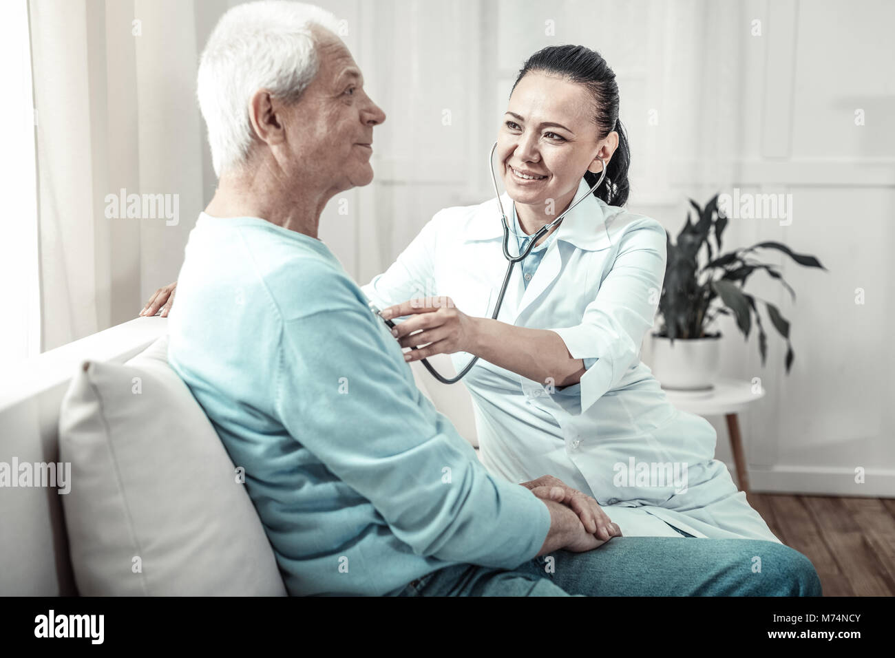Pleasant kind nurse using her stethoscope and smiling. - Stock Image