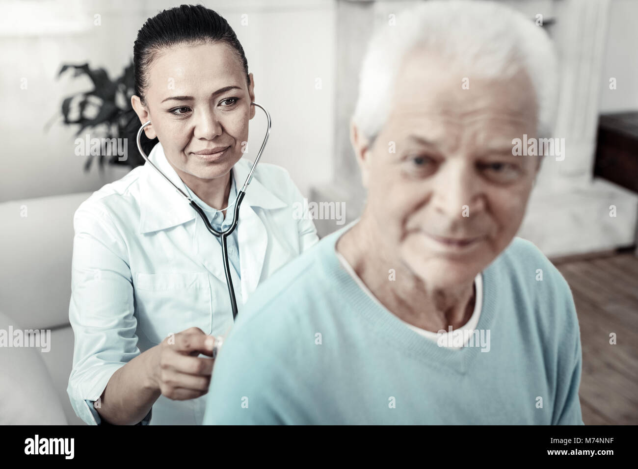 Kind cute nurse examining the patient and smiling. - Stock Image
