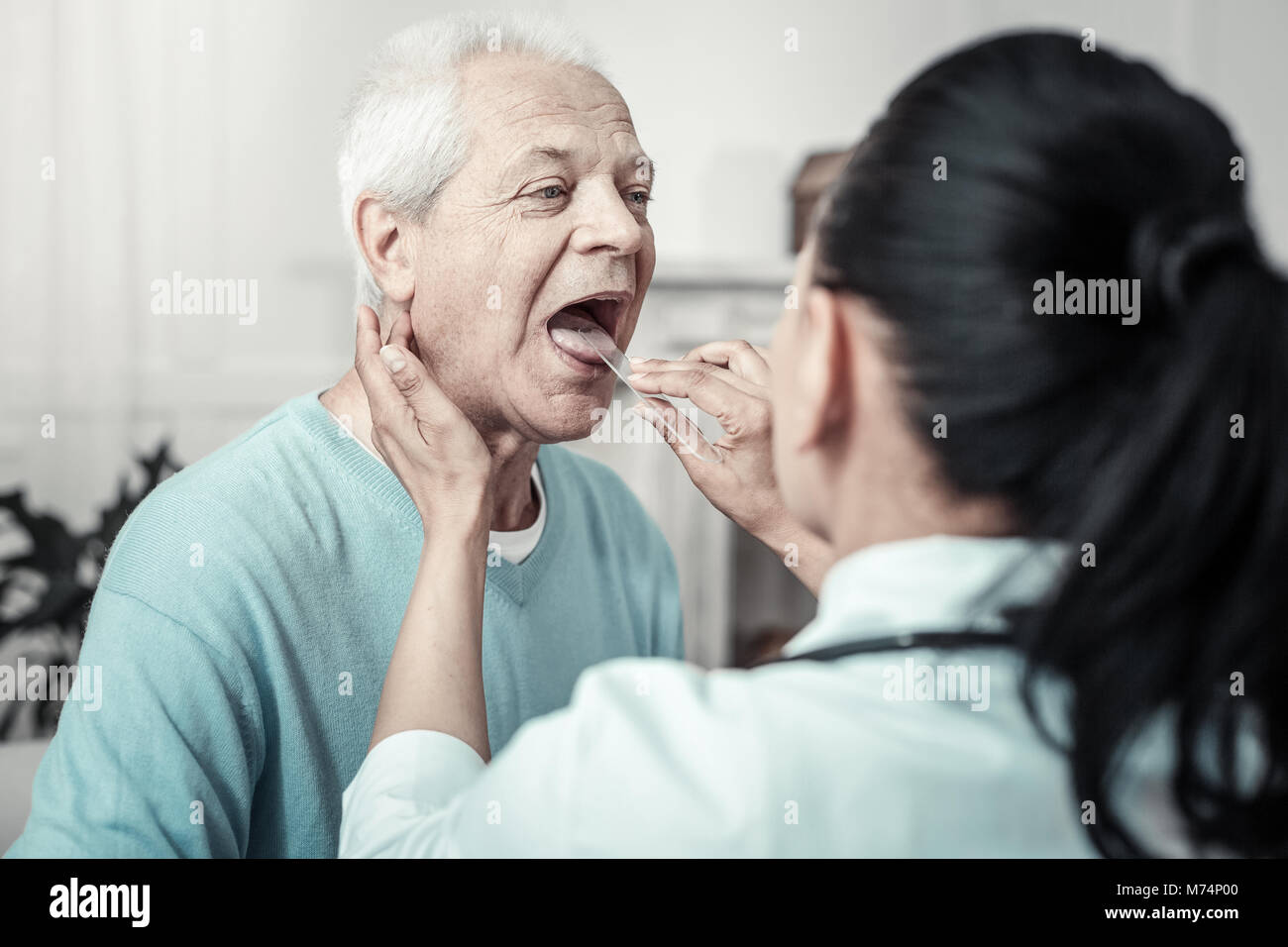 Gray aged man having examination and sitting opposite the nurse. - Stock Image