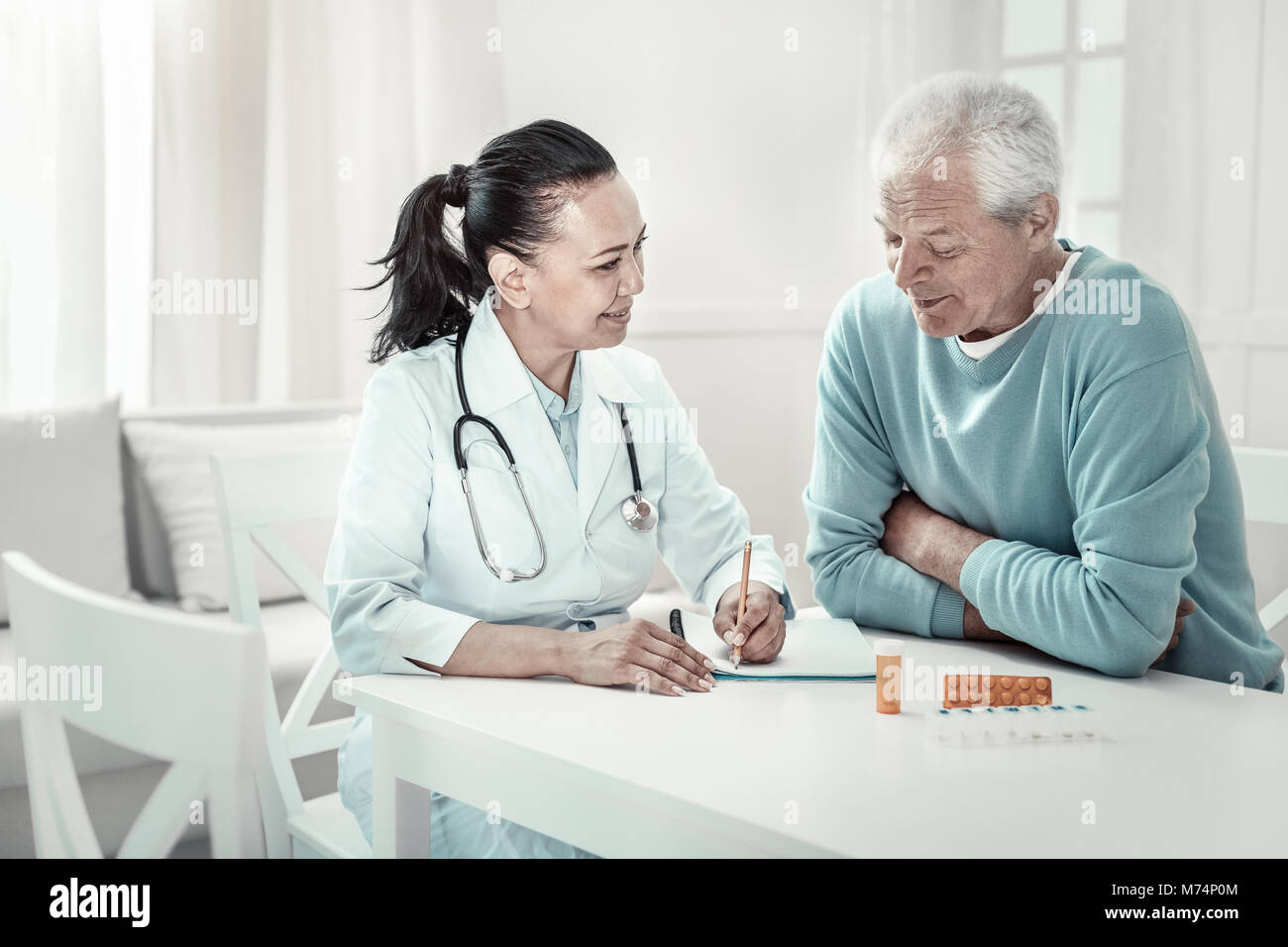 Pretty pleasant nurse giving advices and writing it. - Stock Image