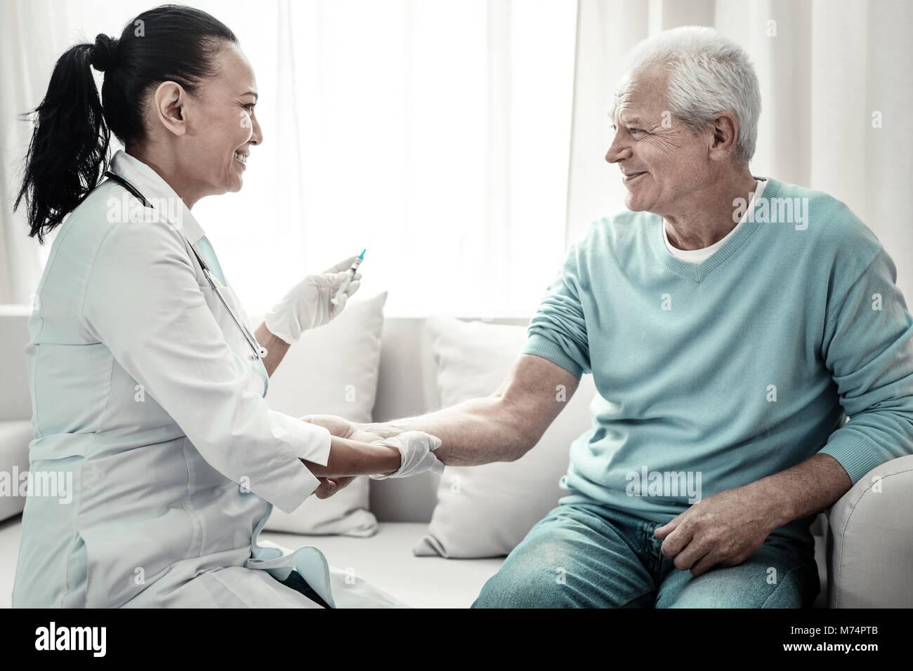 Joyful cute nurse smiling and making injection. - Stock Image