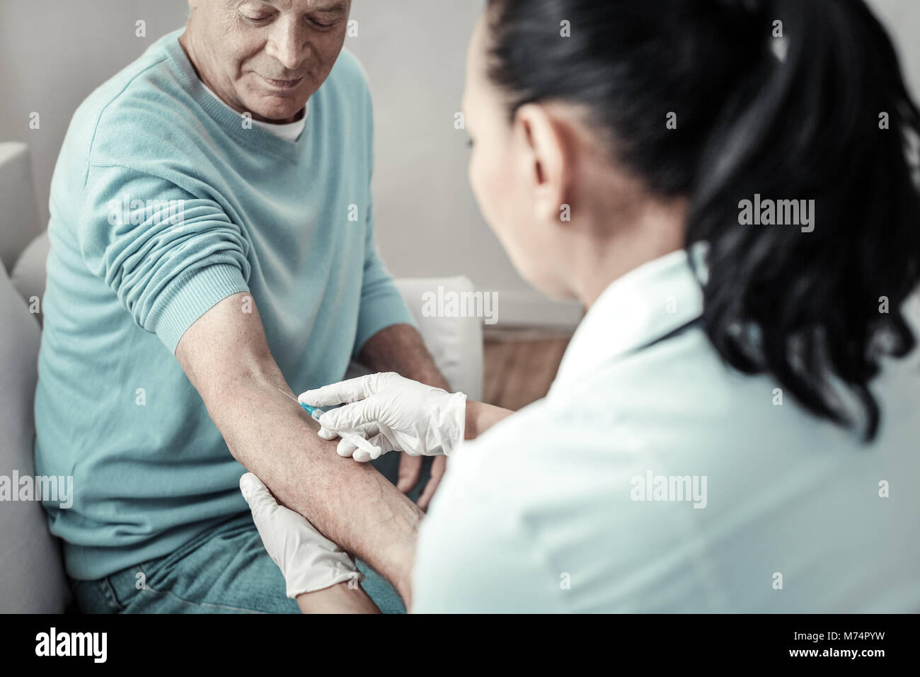 Aged senior patient sitting and having injection. - Stock Image