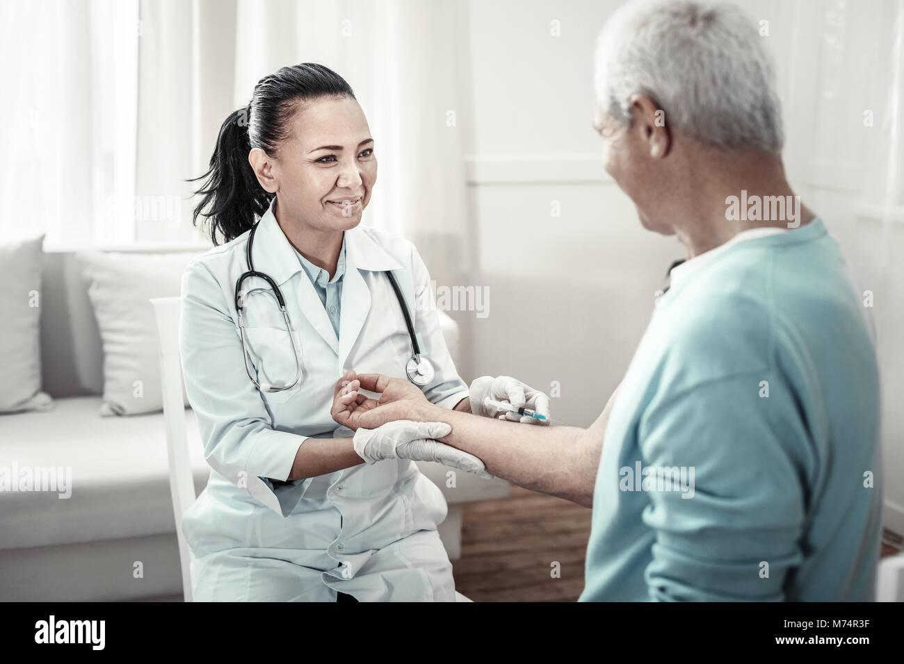 Joyful pleasant nurse smiling and making injection. - Stock Image