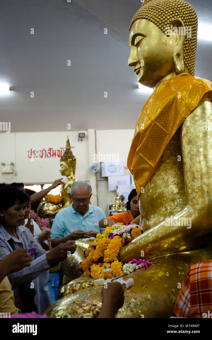 Chachoengsao, Thailand - Aug 7, 2010 : Buddhist donate money and put gold leaf onto buddha at Sothorn temple Chachoendsao - Stock Image