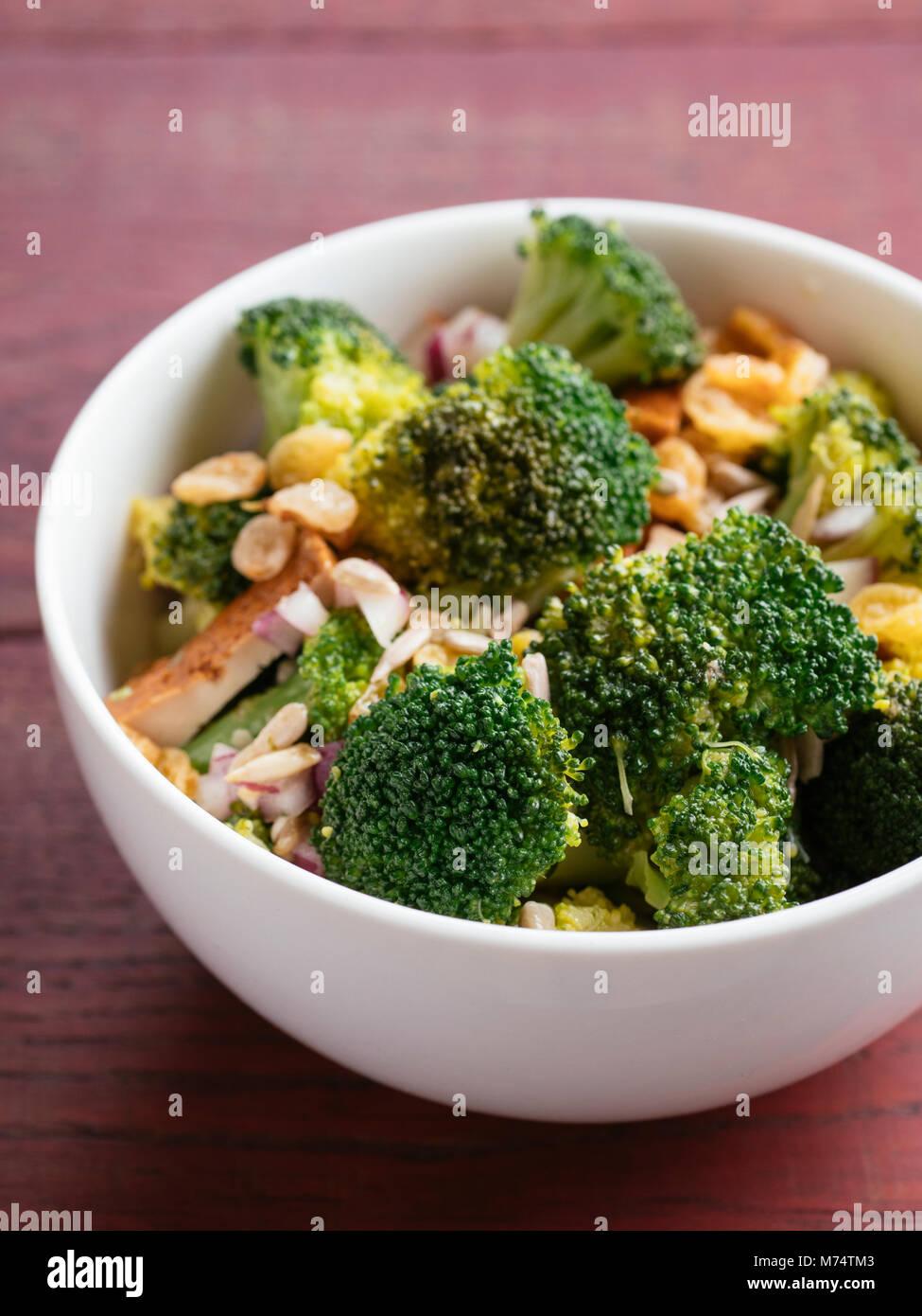 Vegan Broccoli Salad with broccoli, red onion, golden raisins, smoked tofu and sunflower seeds. Stock Photo