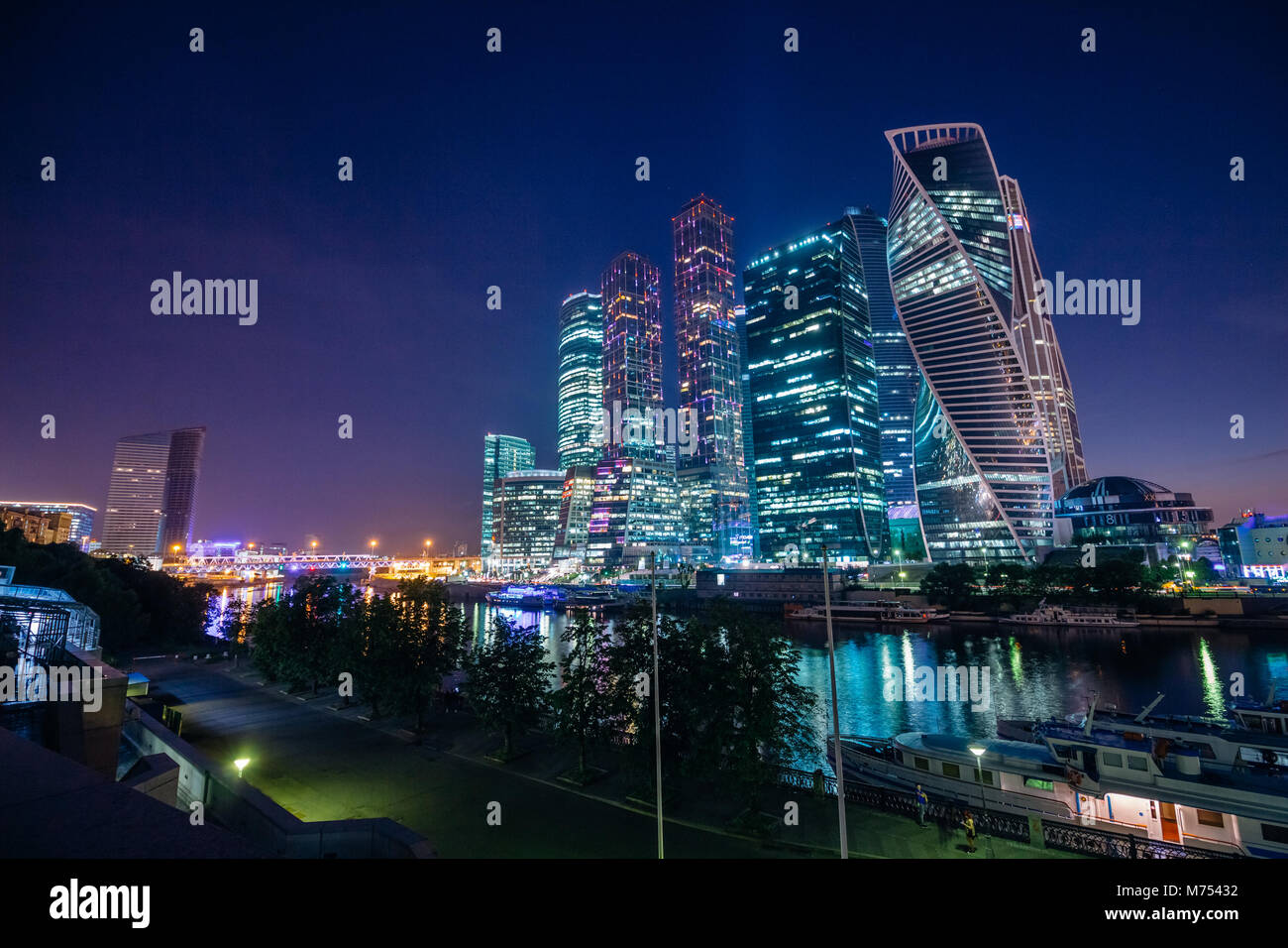 Cityscape with skyscrapers of Moscow City at night with beautiful illumination against the dark blue summer sky - Stock Image