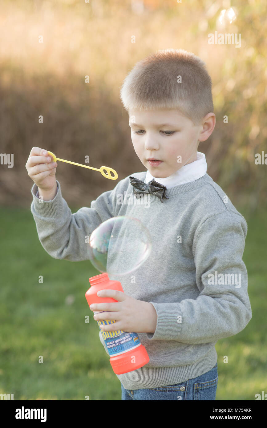 Seven year old boy playing outdoors in the Autumn - Stock Image