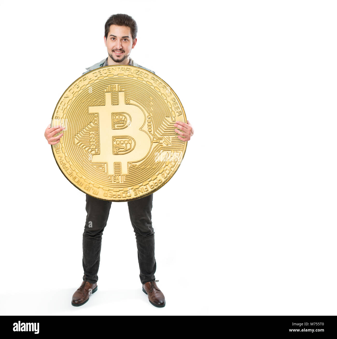 A cheerful man on a white background holding a huge bitcoin coin - Stock Image