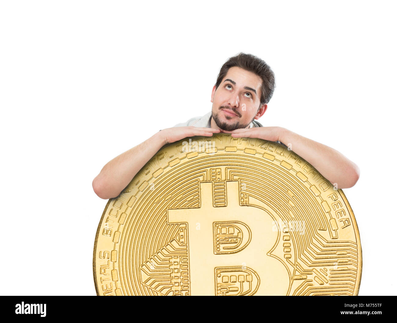 A cheerful man with a big joyful smile holding a huge bitcoin coin on a white background - Stock Image