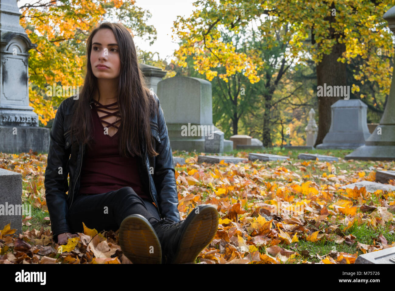 A Young Girl Quiet Reflection, Mourning, Remembering, Meaning of Life and Death, Autumn Season, Surrounded by Leaves, - Stock Image