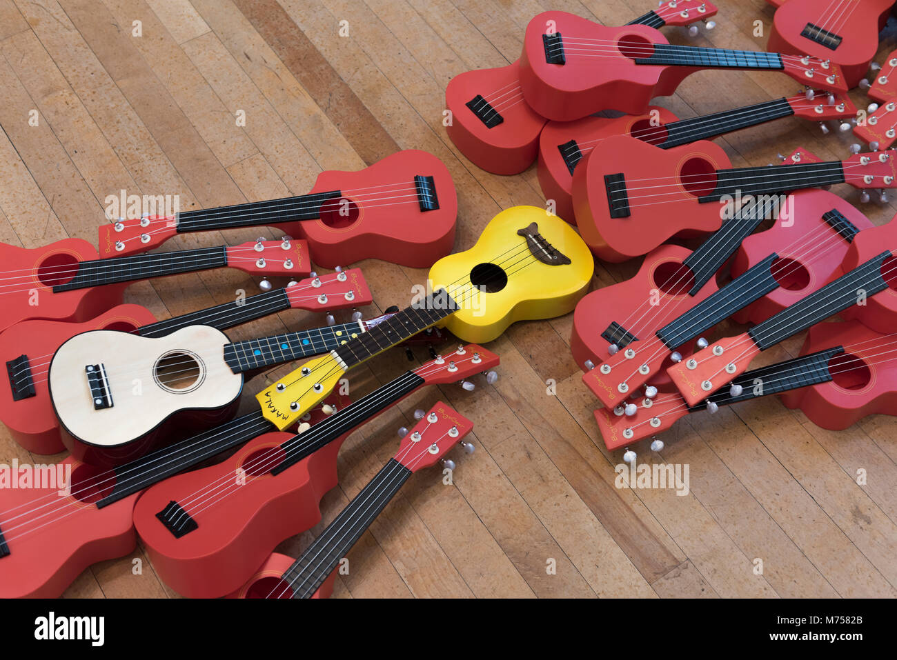 Collection of entry level ukuleles and small guitars lying on the floor before a junior music lesson with children - Stock Image