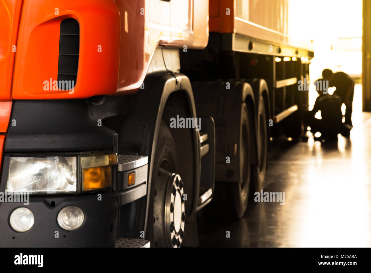 automobile mechanic checking truck in the garage in the moning with sumbeam, selective focus - Stock Image