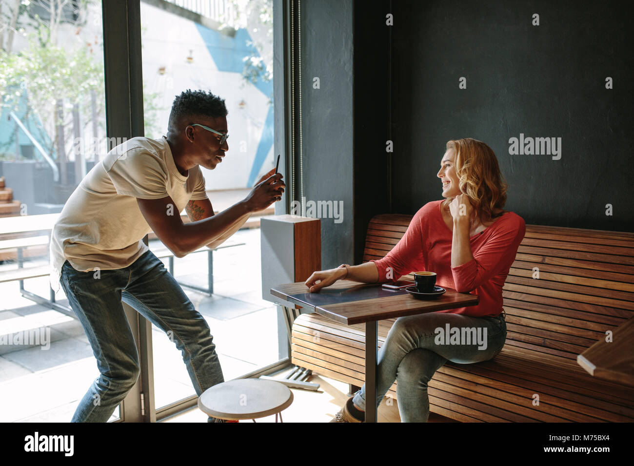 Woman sitting at a coffee shop posing for a photograph. Man taking photo of a woman using mobile phone at a coffee - Stock Image