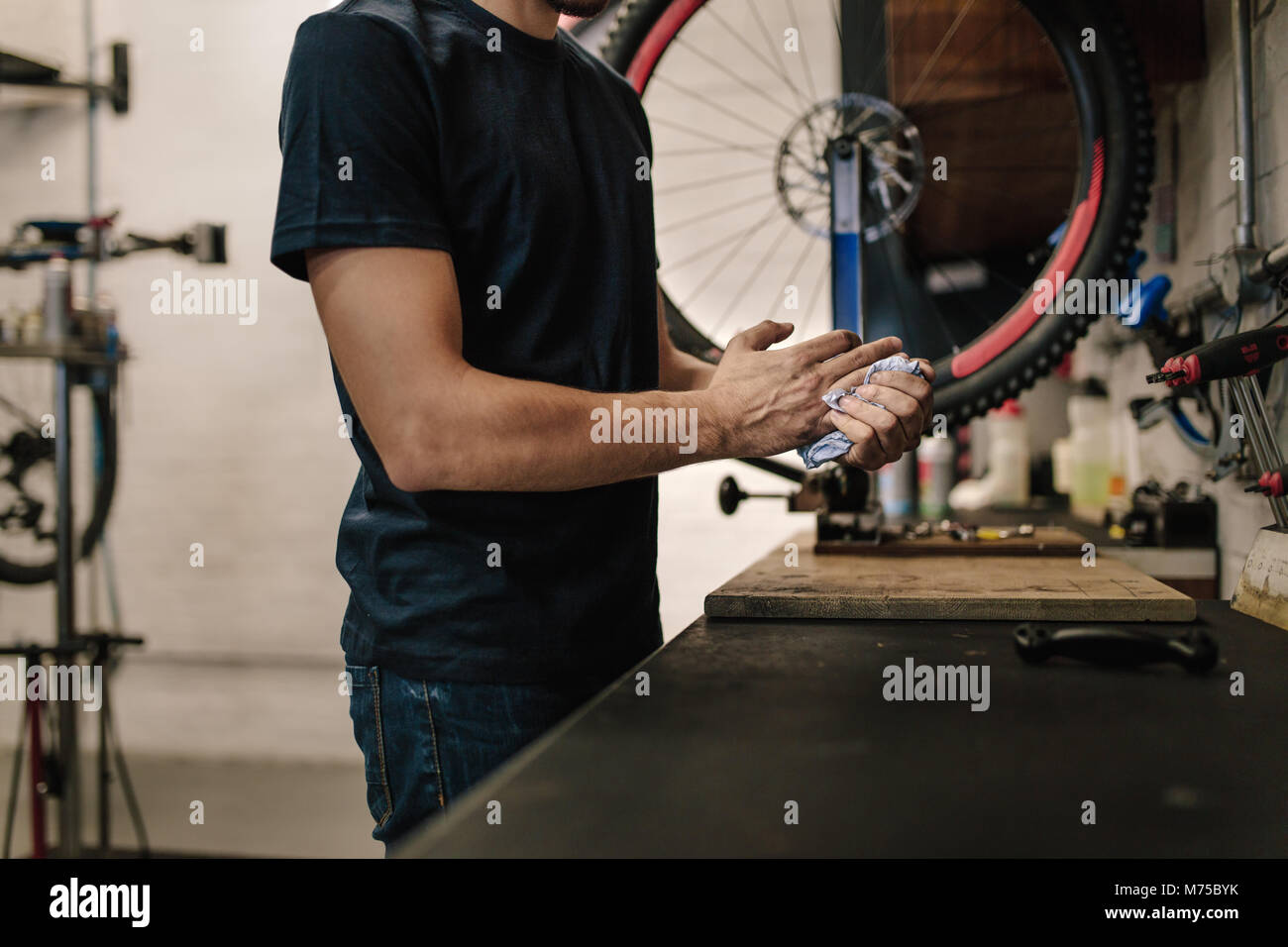 Worker cleaning his hands after repairing bicycle in