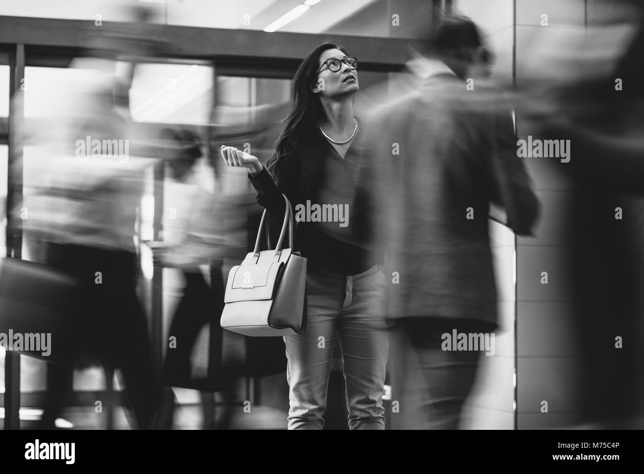 Asian businesswoman waiting for someone with people rushing in the lobby. Motion blur effect. Black and white shot. - Stock Image