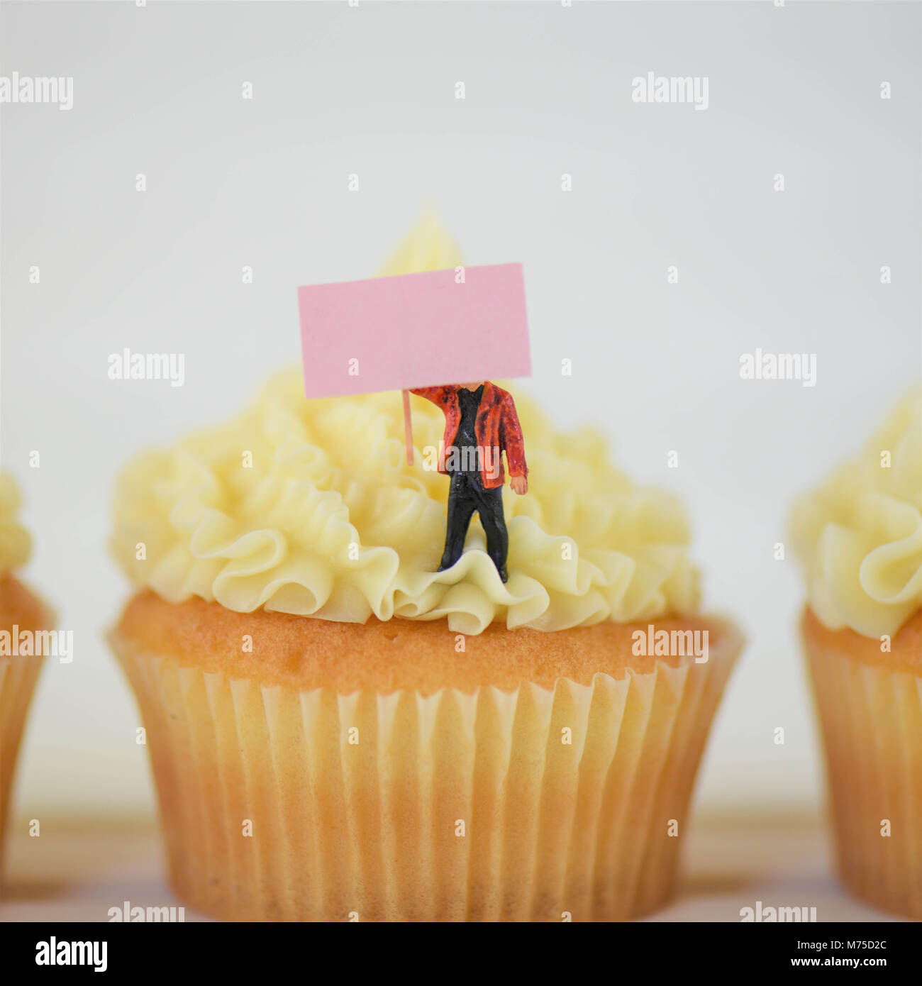 home made cakes with miniature person holding a blank sign for note - Stock Image