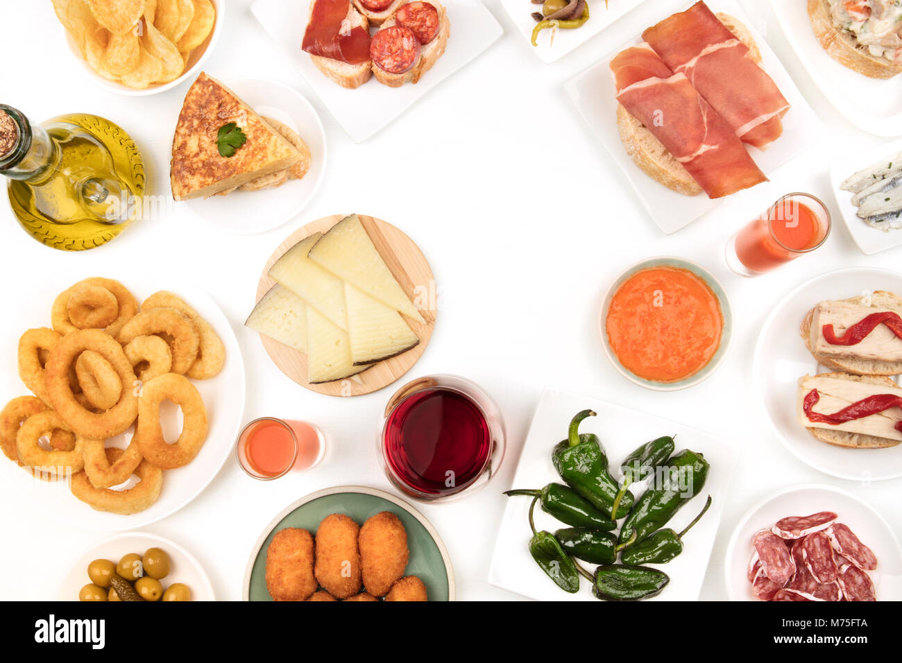 An overhead photo of Spanish tapas, forming frame on white with copy space - Stock Image