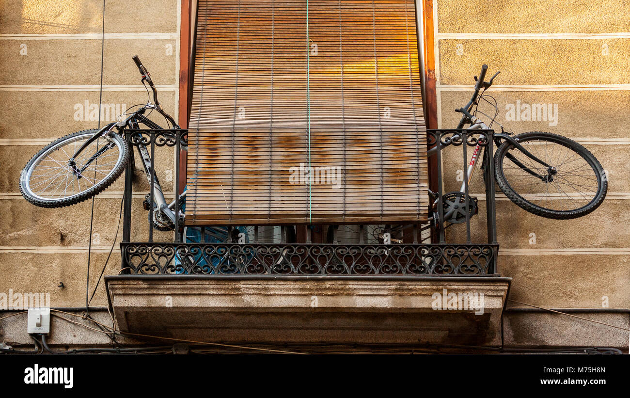 two bicycles stored on a narrow balcony of a tenement in Madrid, Spain - Stock Image