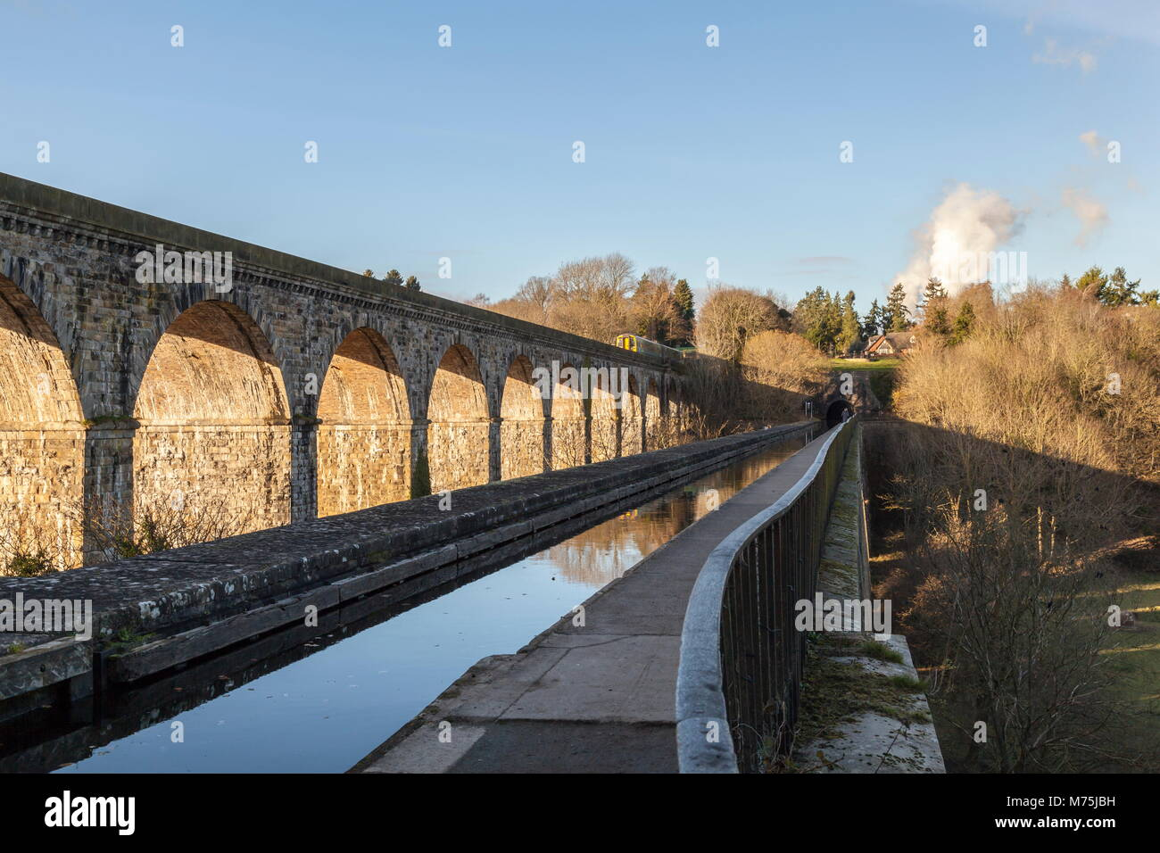 A passenger train crosses over the viaduct while viewed from the aqueduct towpath of the Llangollen Canal, Ceiriog - Stock Image